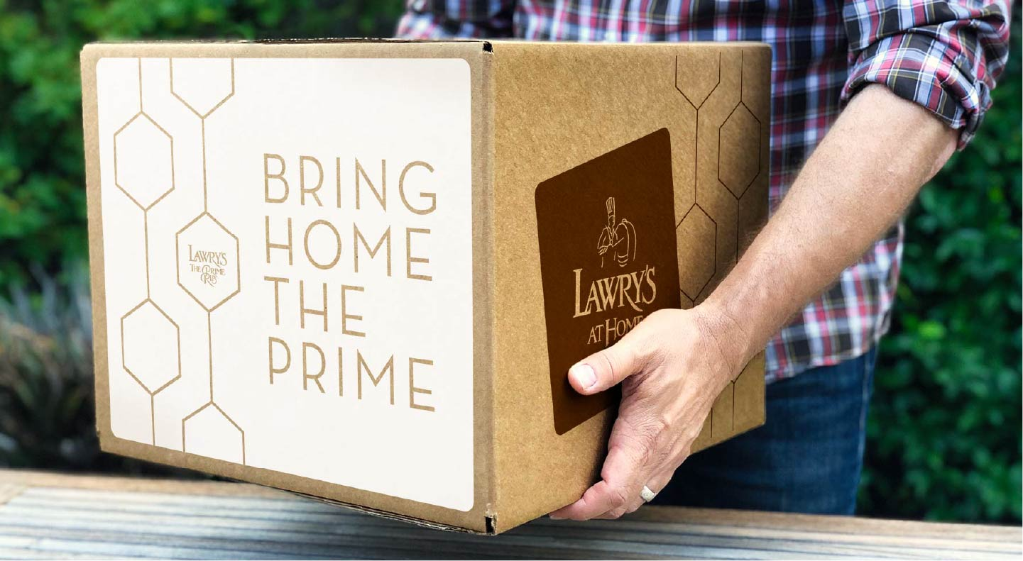 man carrying a shipping box labelled Bring Home the Prime