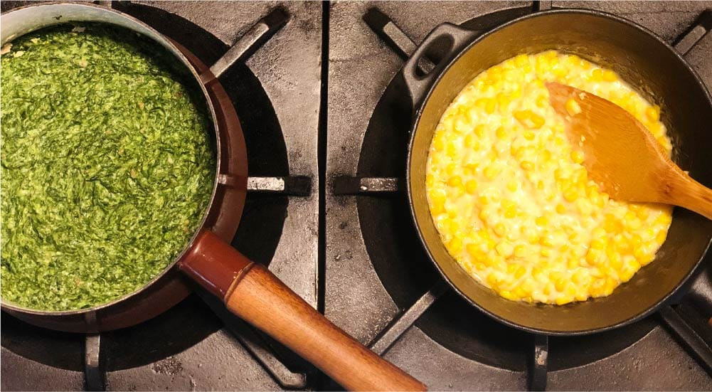 saucepans on a stove with creamed corn and creamed spinnach