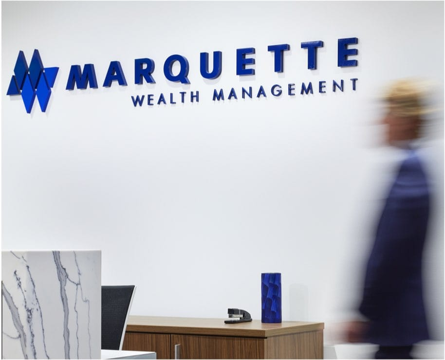 man walking past a blue sign in an office lobby