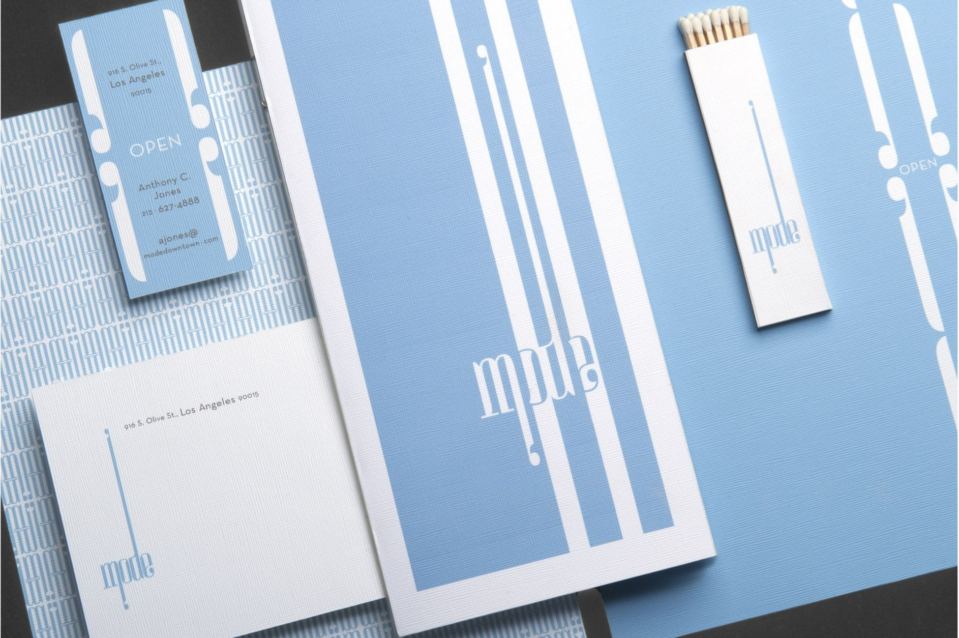 brand identity package with a business card, menu card, matchbox, and stationery
